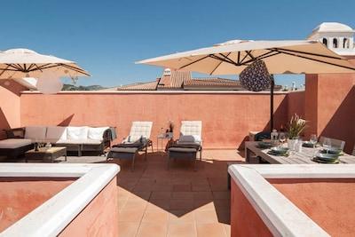 Big solarium with sun loungers, lounge area, dining area,...