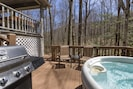 Hot tub and gas grill area off back of the cabin