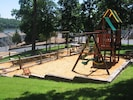 Playground, picnic tables and charcoal grills in this common ground area.