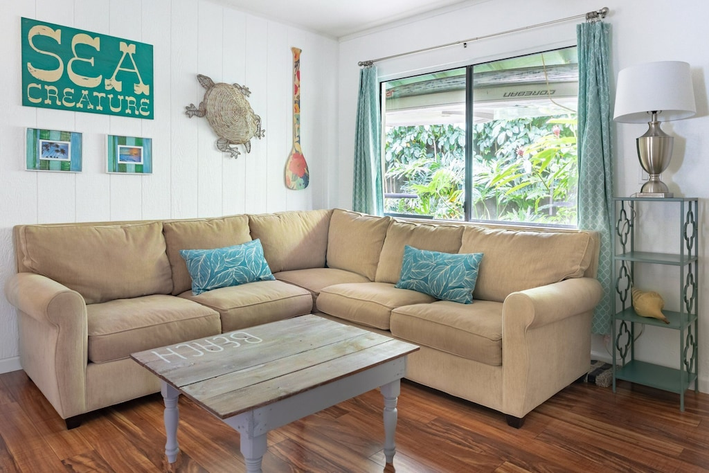 Living room of a Maui Airbnb featuring hardwood floors, turqoise accents and a turtle for decoration
