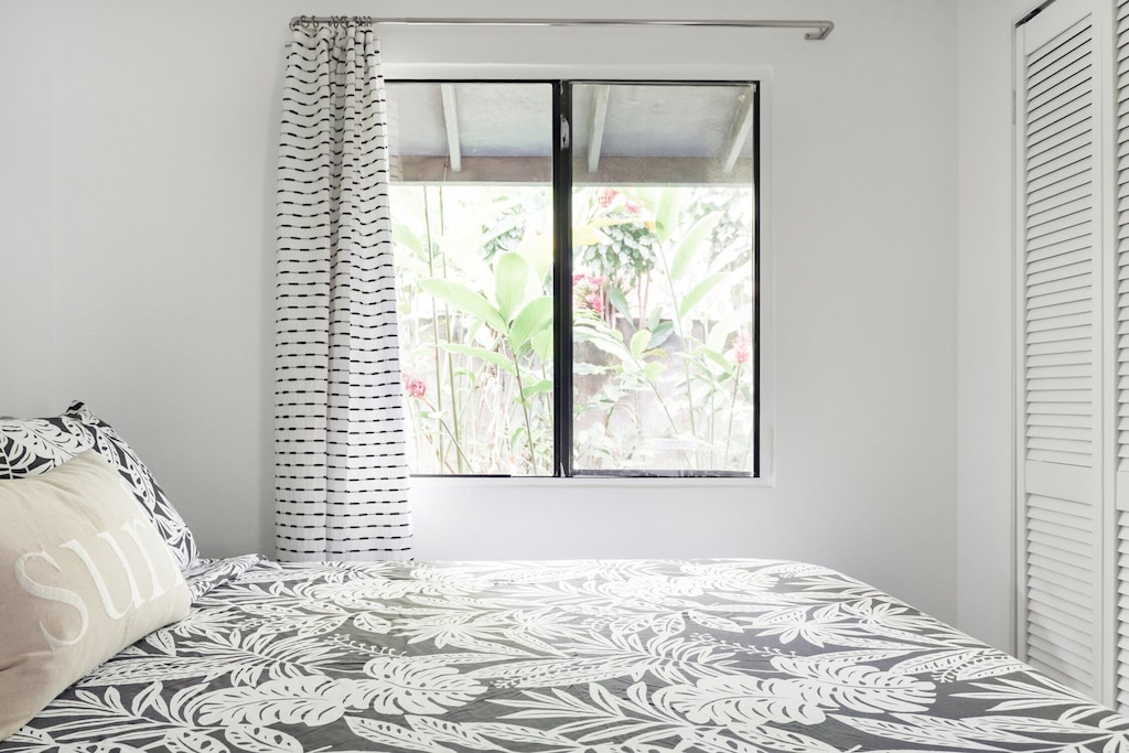 Bedroom of an Airbnb in Maui with a window view of tropical vegatation