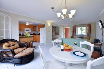 Dining Room Set for 2 in the Foreground with Background View of the Living Room and Front Door