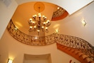The custom spiral staircase ascends from the foyer to the 3rd floor.