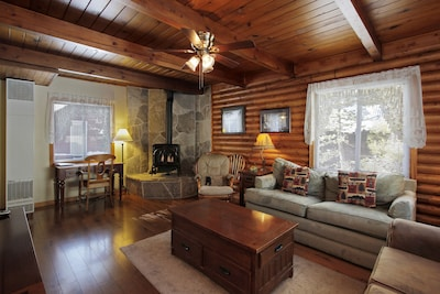 Beautiful living room with Tahoe Stone Hearth and original log walls.
