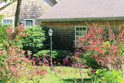The cottage is surrounded by flowering perennials and shrubs.