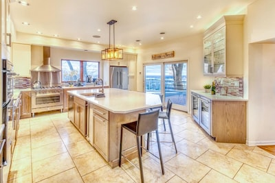 The Gourmet Kitchen features a large island, gas/electric ovens, two dishwashers, and a wine bar.