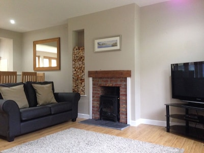 Spacious open plan living area with log burning stove