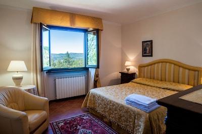 Camera da letto matrimoniale con panorama sulla Toscana