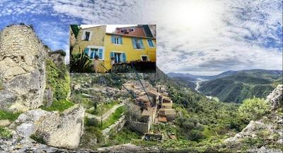 la maison (Mur pierre et jaune) se situe au pied des ruines du chateau