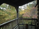 Leaves begin to turn in fall in the wooded area surrounding the back deck