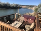 Firepit table and lounge with hot tub and river.
