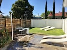 Private backyard with turf grass and ranch swim tank.