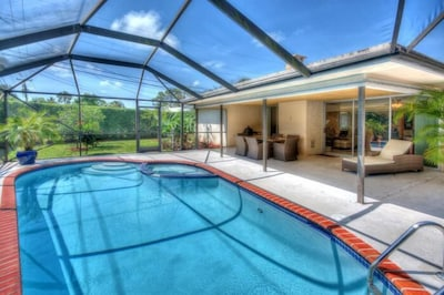 Screened-in heated pool with barbecue area.