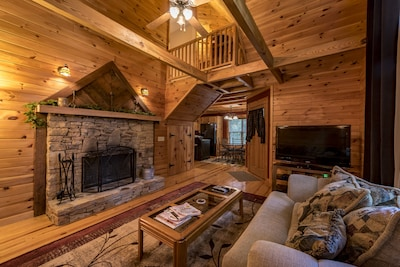 Two story great room with exposed beams, view of upstairs bedroom and kitchen.