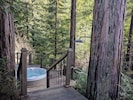 The hot tub set in the middle of a tranquil ring of redwood