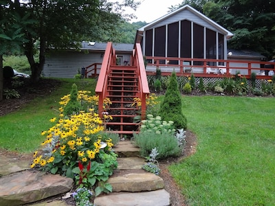 The CreekHouse front view with stairs leading to the spectacular screened porch