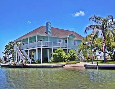 Side view showing stairway to entrances and private lighted fishing dock and boat ramp.