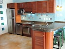 Modern kitchen with full sized appliances, granite countertop and tiled wall.