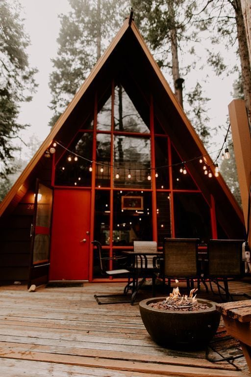 String lights hang over the outdoor eating area and the propane fire pit