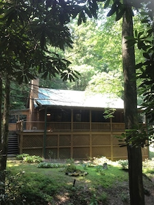 The cabin is tucked away in a hardwood forest cove...