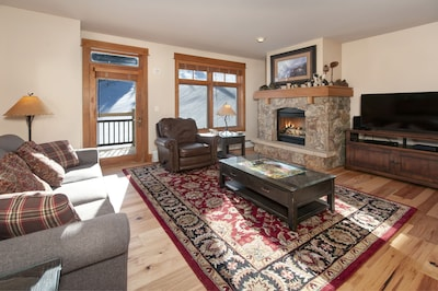 Living Room with moss rock fireplace, HDTV and queen sofa bed.
