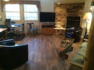 Flat screen TV, wood tile, fireplace.
