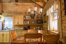 Country style dining table with fully stocked kitchen utensils and appliances.