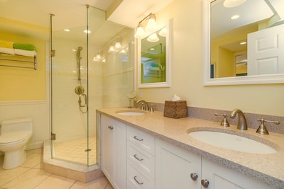 Bathroom Has a Spacious Walk-In Glass Shower And Double Sink Quartz Vanity