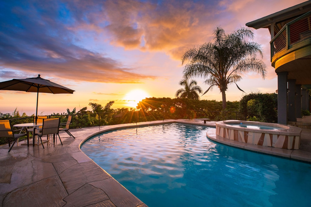 Amazing sunset over the pool of this Big Island house rental