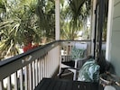 Front deck with bar height table and chairs nestled in palm trees