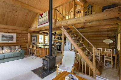 Main living space with wood Stove. Steps up to the loft and down to bedrooms.