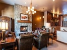 Great room with TV in armoire, gas fireplace, and wet bar.