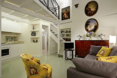 Living Room with double sofa bed, armchair, TV and full kitchen.