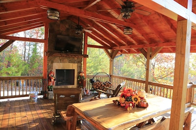 Covered deck with large tv, ceiling fans, rockers, and a view for family fun
