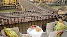 Terrace is narrow but has a table and two chairs. The Arno river is below.