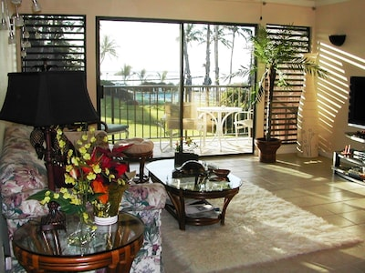 Living room with view of pool, fishpond, ocean, and island of Lanai