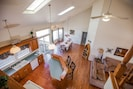 View from loft of dining, kitchen, living room and sliding glass door to deck