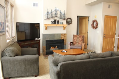 """Warm inviting living area with fireplace and 55"""" TV"""