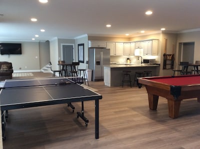 Game room with kitchen, pool table, ping pong, and two 70 inch Televisions !
