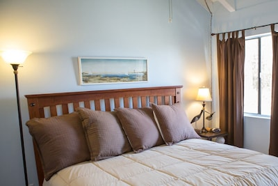 Master beach-themed bedroom with vaulted ceiling, tv, King Bed, & master bath