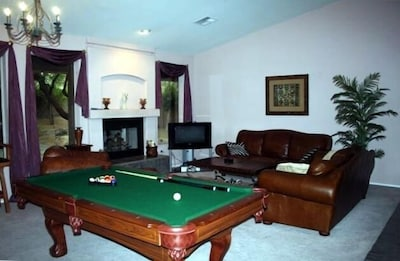 Living room w/2 santa fe leather couches & leather cognac chair & pool table.
