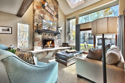 """Living room with soft club chairs and sofa, gas fireplace, and 50"""" HD DVR TV."""