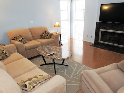 Comfortable and spacious living room with fireplace and HDTV