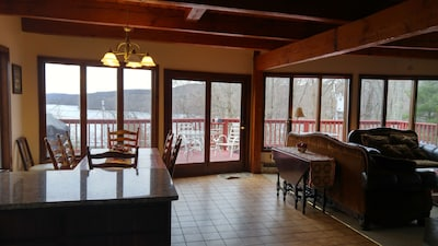 Living room open to surrounding deck and lake view