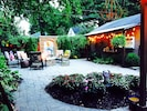 Charming backyard view of from the outdoor dining area and hanging basket swings