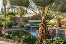 Lush landscape surrounds the perimeter of the pool