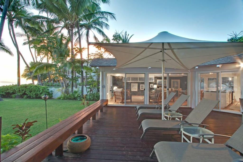 Terrace and lawn of a Maui holiday home at sunset