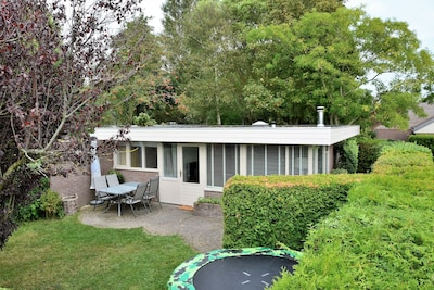 Bungalow met trampoline in de tuin.
