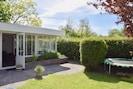 Zonnige tuin met veel privacy, eettafel met stoelen, ligbedden en trampoline.