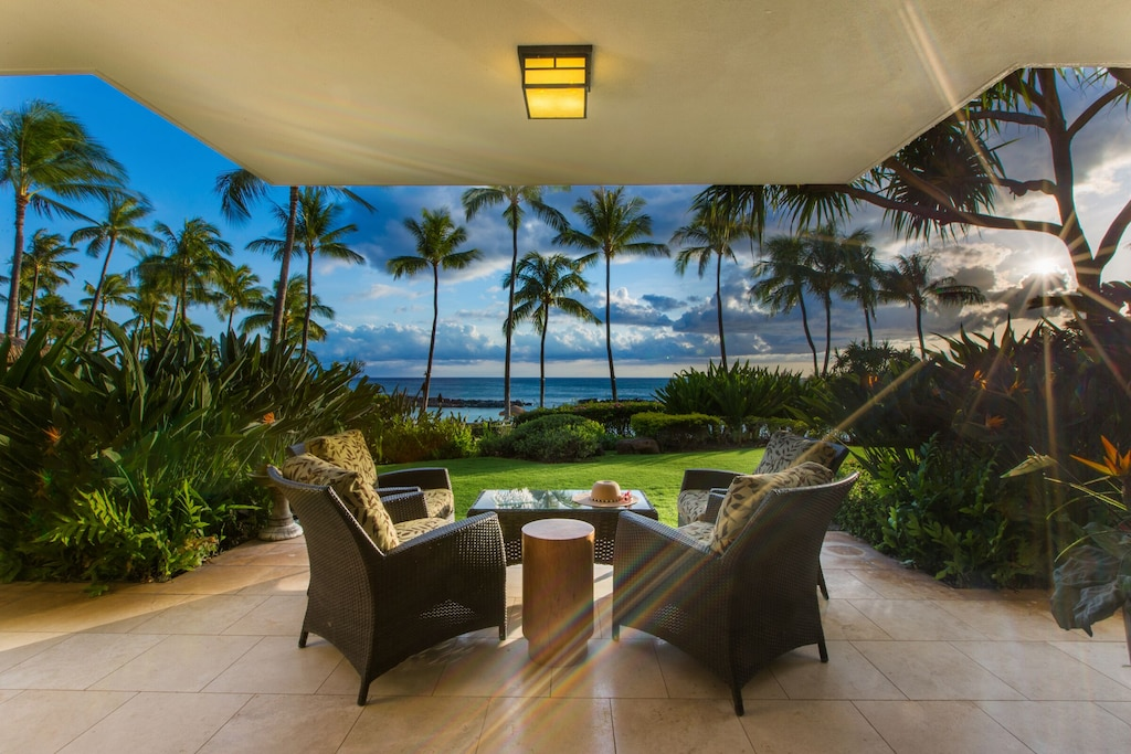 Tropical decor and ocean views from a spacious lanai equipped with chairs and a table